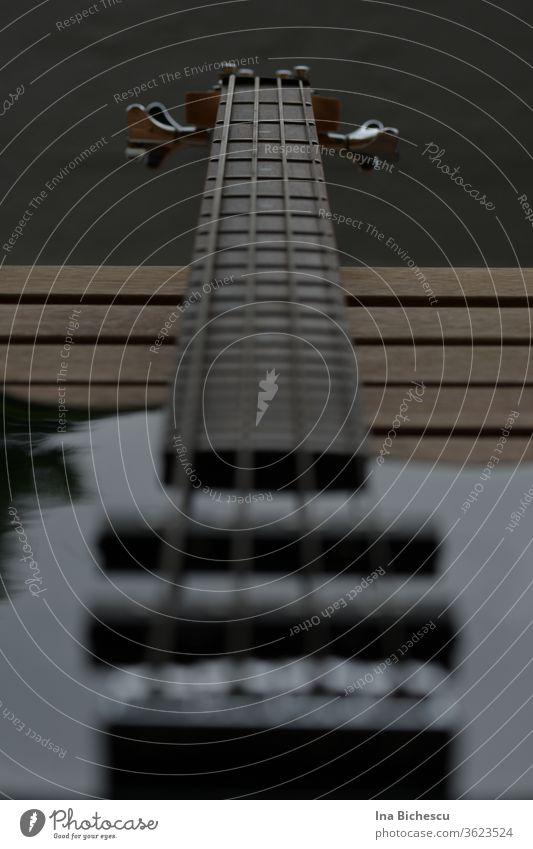 Ein E-Bass Hals fotografiert von Seitenhalter Richtung Kopf. Das Instrument ist schwarz, der Fokus liegt auf dem Griffbrett und auf den vier Seiten. EBass