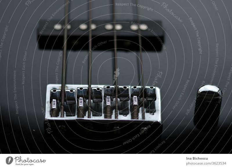 Der Seitenhalter einer schwarzem E-Bass mit vier Seiten und ein Knopf sehr nah fotografiert. Das Bild ist fast komplet schwarz, nur das Metal des Seitenhalters und der Knopf glänzen und erhellen das Bild.