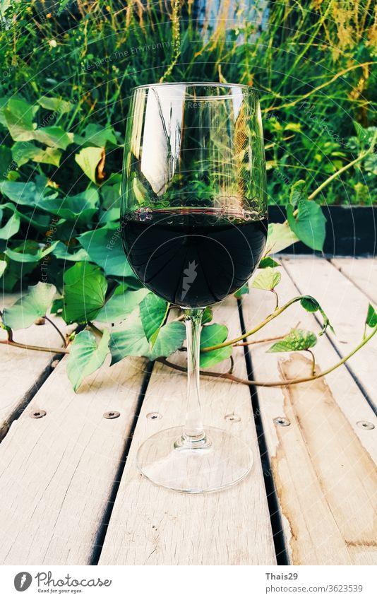 Glas Rotwein auf hölzernem Hintergrund Garten im Freien Alkohol alkoholisch Bar Lauf Getränk Flasche Feier Nahaufnahme Kultur trinken Lebensmittel Traube