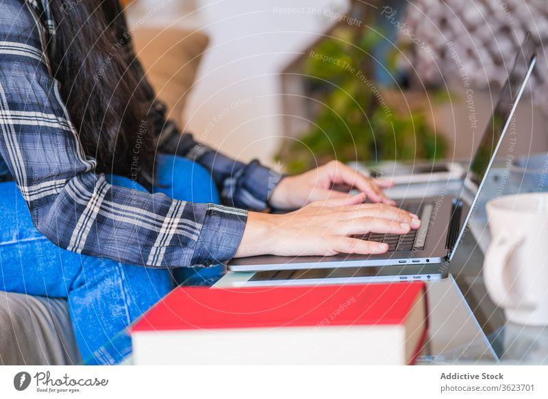 Junge Frau arbeitet mit Laptop im Wohnzimmer heimwärts benutzend Arbeit freiberuflich Sofa jung lässig abgelegen Gerät Apparatur Browsen Internet Lifestyle