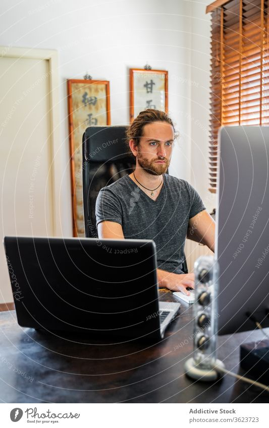 Hübscher Mann arbeitet zu Hause am Desktop-Computer Tippen Keyboard freiberuflich heimwärts abgelegen Arbeit benutzend männlich ernst Projekt beschäftigt
