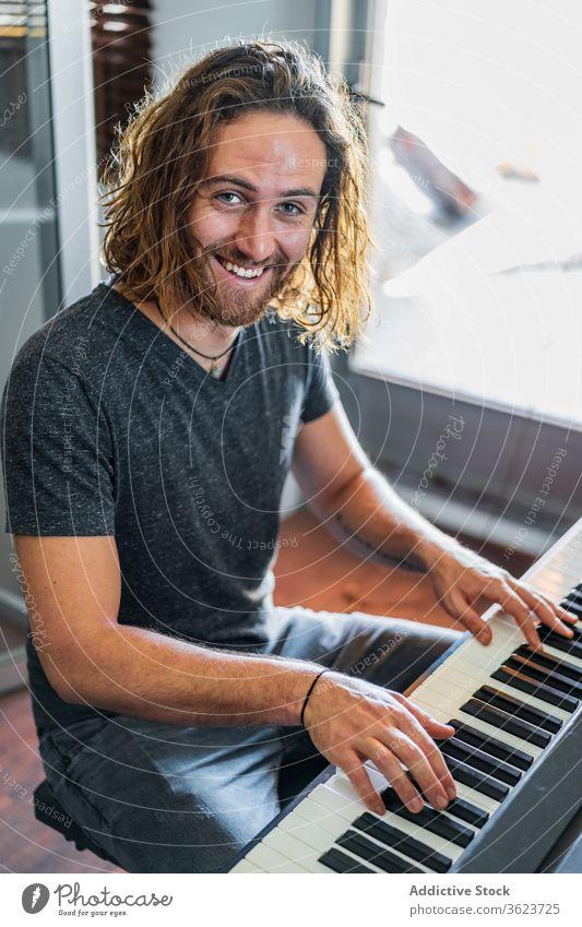 Talentierter Mann spielt zu Hause Klavier spielen Synthesizer Musiker Instrument heimwärts elektronisch männlich Fähigkeit Appartement gemütlich sitzen Melodie