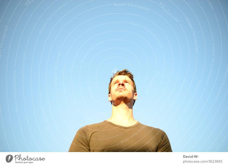 Mann schaut nach oben in den blauen Himmel und hat einen fraglichen Gesichtsausdruck schauen Blick nach oben nachdenken überlegen Gedanken Hintergrund
