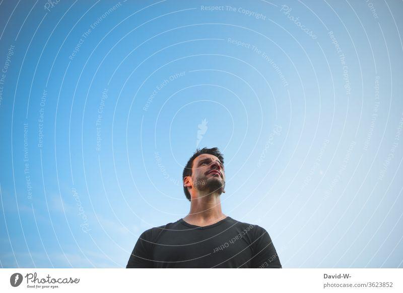 Mann schaut nachdenklich in den Himmel - Blick nach oben schauen nachdenken überlegen Gedanken blau Hintergrund Hintergrund neutral neutraler Hintergrund