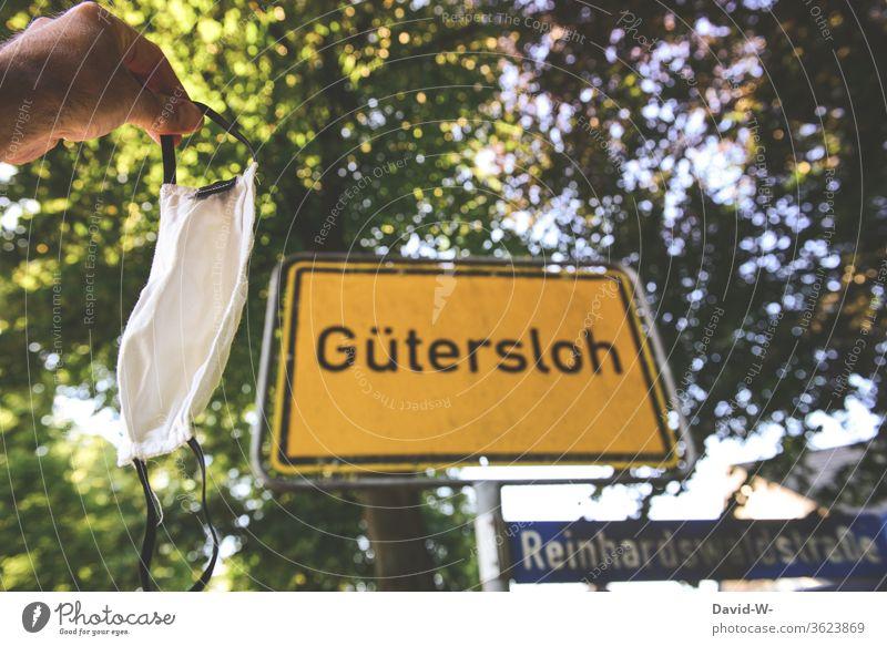 Mann hält aus Hinweis eine Atemschutzmaske vor das Ortsschild in Gütersloh - Corona / covid-19 Ortsschild - Gütersloh Rheda-Wiedenbrück Oelde Absperrung