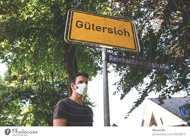 Mann mit Atemschutzmaske in Gütersloh - Ortsschild - Corona / covid19 Rheda-Wiedenbrück Oelde Absperrung abstand halten sicherheit covid-19 Tönnies Hotspots