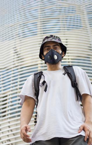 Ein junger Mann im Freien mit einer schützenden Gesichtsmaske zum Schutz vor einer Infektion mit dem Coronavirus, der während einer globalen Pandemie eine mit Blumen bedruckte Eimerkappe und einen Beutelpack trägt.