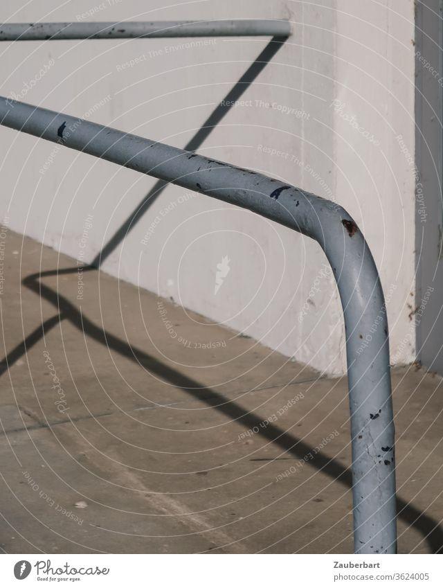 Der Schatten einer grauen Haltestange aus Eisen wirft Linien auf Wand und Pflaster Stange Straße Mauer Beton weiß Muster abstrakt halten greifen Kurve