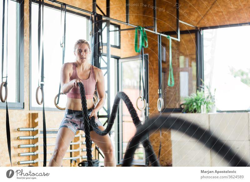 Junge Frau in der Turnhalle beim Crossfit-Training an den Seilen schön Stärke zäh Gerät Fitnessstudio Sport sportlich Ausdauer passen attraktiv Abwechselnd