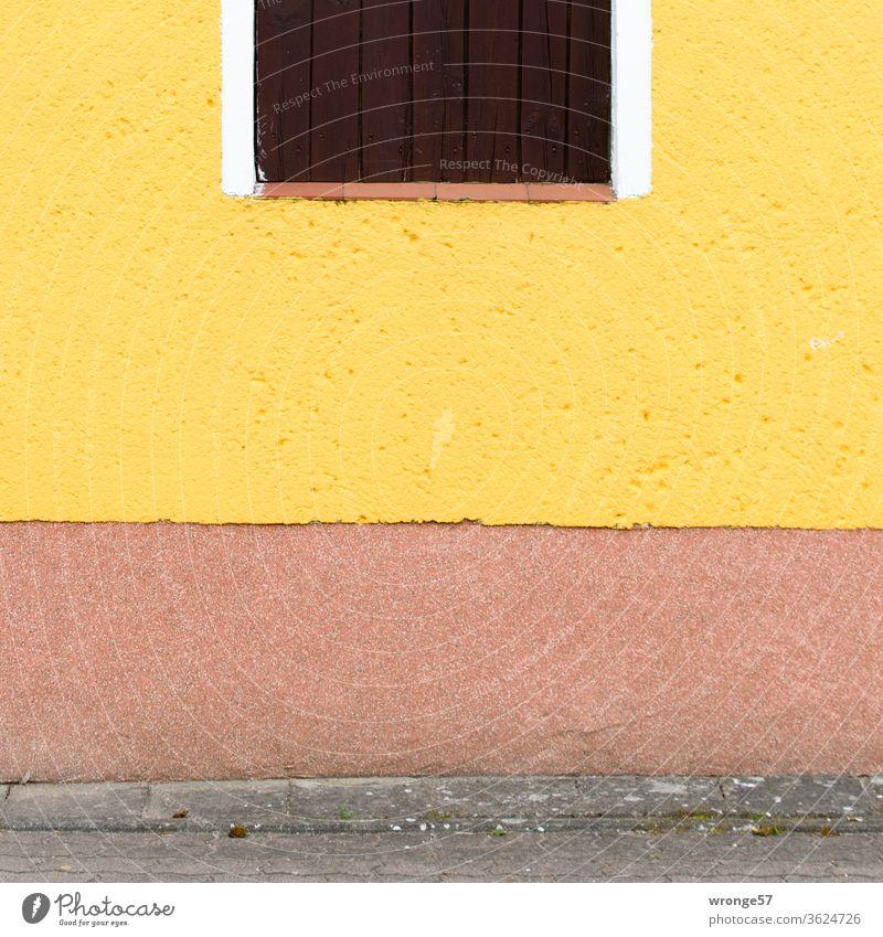 Farbenfrohe mit gelber Farbe gestrichene Hauswand und einem teilweise abgebildeten Fenster. Fassade gelbe Farbe Gebäude Wand Außenaufnahme Menschenleer Mauer