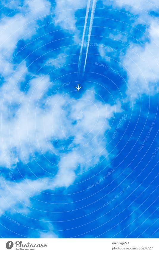 Passagierflugzeug mit Kondensstreifen fliegt hoch oben am leicht bewölkten blauen Himmel Flugzeug hochoben mehrstrahlig Luftverkehr Ferien & Urlaub & Reisen