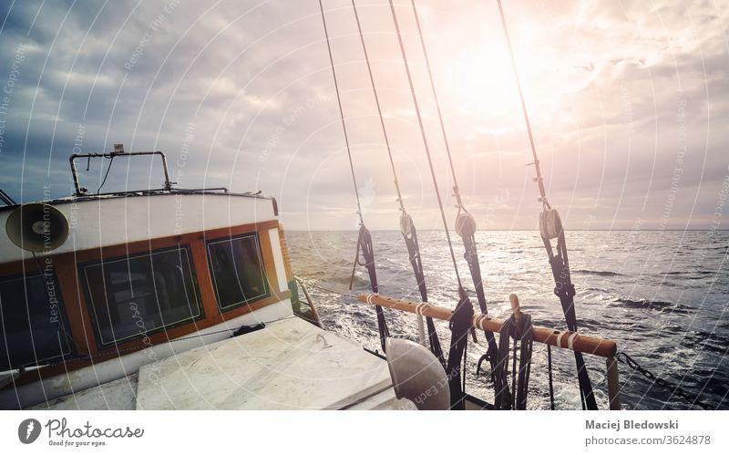 Ein altes Segelboot auf dem Ozean bei Sonnenuntergang. Wasser Natur Jacht Boot Schiff Segeln Wind Himmel romantisch Horizont winken Urlaub Sonnenlicht Sport