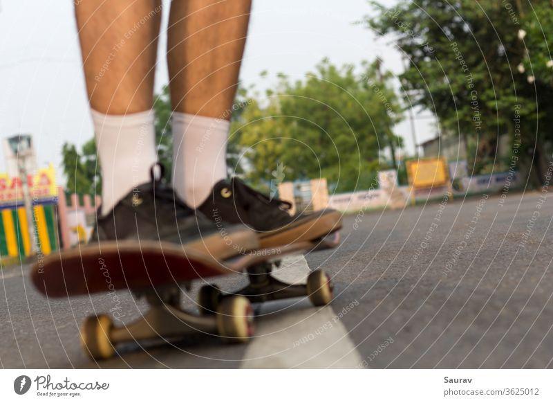 Verschwommene Nahaufnahme der Füße von jemandem, der auf einem Skateboard auf einer leeren Straße fährt. Skateboarding Erholung Lifestyle leere Straßen Sommer