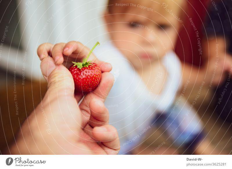 Kind bekommt vom Vater eine Erdbeere Erdbeerzeit Frucht Leckerbissen schön Beerenfrucht obstsorten Obsttorte gesammelt Sammler Sommertag sommerlich ernten