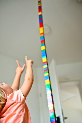 Kind baut mit Bauklötzen im Kinderzimmer einen riesigen Turm und zeigt begeistert mit den Fingern an die Decke bauen Spielsachen Spaß Freude euphorisch Euphorie