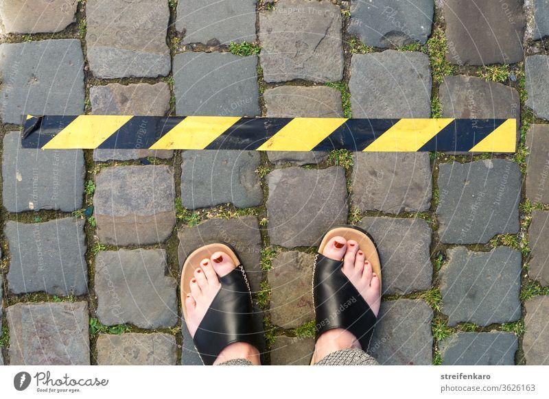 Abstand halten! - weibliche Füße stehen vor einem schwarz-gelben Klebeband auf Kopfsteinpflaster Corona Corona-Virus Schutz Pandemie Infektionsgefahr Gesundheit