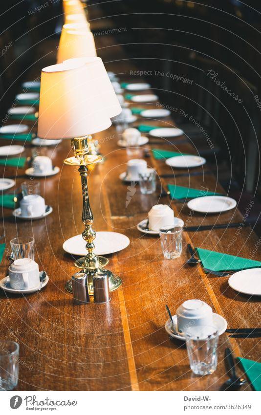 ein gedeckter Tisch / Tafel mit leeren Plätzen corona abstand aufgedeckt Geschirr Lampenlicht Einladung Treffen Business meeting Leere verlassen Pandemie