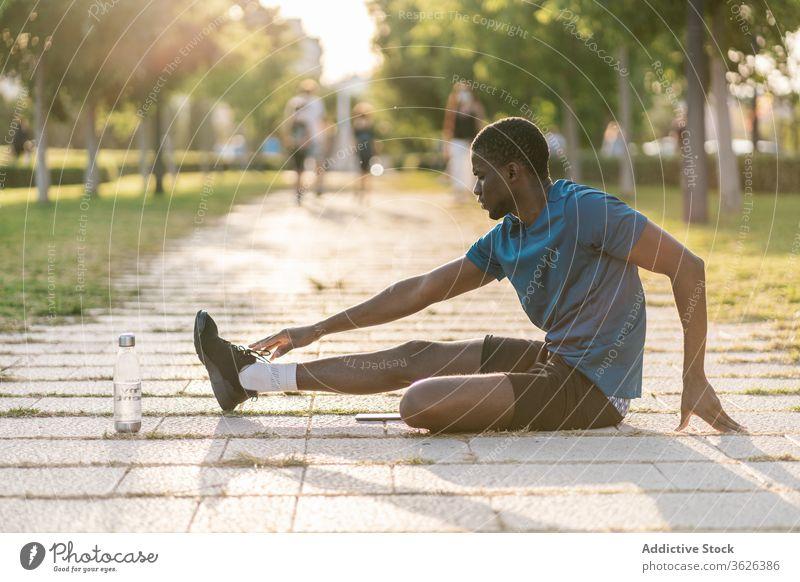 Athletischer schwarzer Mann trainiert im Park männlich Fitness Training Sport Läufer Dehnübung trainiert. Flexibilität Gesundheit Lifestyle strecken jung passen