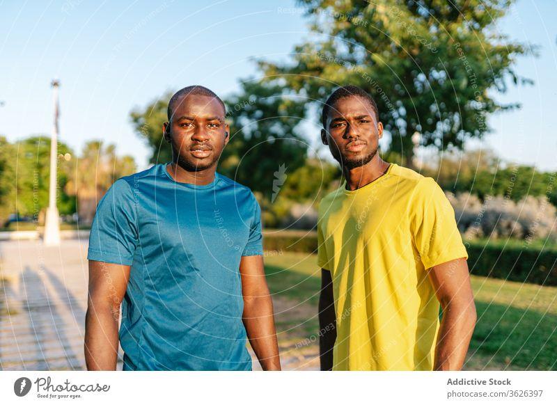 Zwei schwarze Männer beim Selbstmord Glück Park männlich im Freien Lächeln Afrikanisch Menschen jung Fröhlichkeit heiter Erwachsener Freunde Porträt Jugend