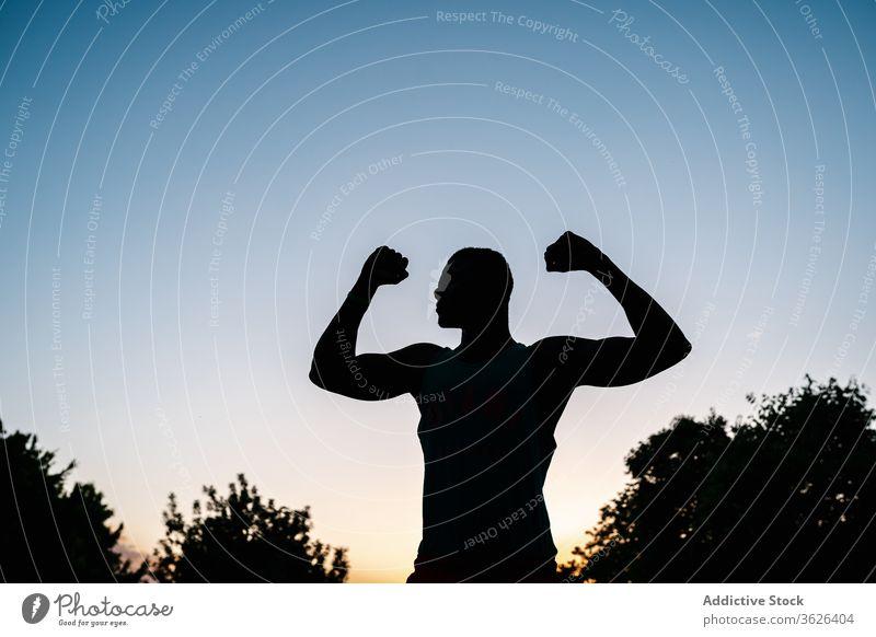 Athletischer schwarzer Mann trainiert im Park Afrikanisch muskulös Silhouette Fitness stark Biegung Körper passen Muskel Bizeps Waffen Stärke Lifestyle Truhe