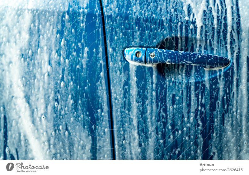 Blaue Autowaschanlage mit weißem Seifenschaum. Autopflege-Geschäft. Autowasch- und Glanzservice vor dem Wachsen. Fahrzeugreinigungsdienst mit Antiseptikum und Desinfektion des Coronavirus (COVID-19). Autowaschanlage.