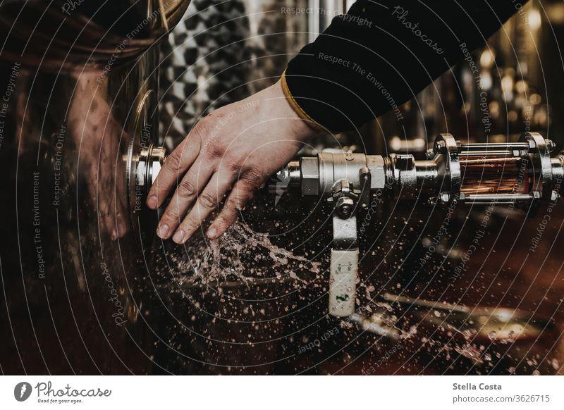 Winzer entfernt den Schlauch der Abfüllanlage und der Wein spritzt umher Innenaufnahme Menschenleer Alkohol abfüllung Farbfoto Schwache Tiefenschärfe