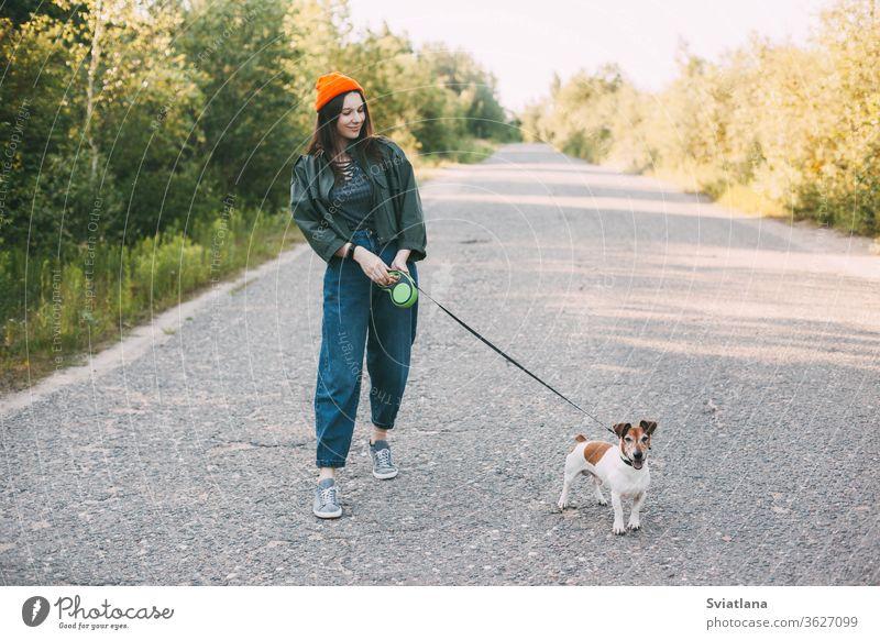Süßes modernes Teenager-Mädchen in grüner Jacke und orangem Hut geht mit ihrem Hund in der Natur spazieren. Haustier, Pflege, Freundschaft. Park jung laufen