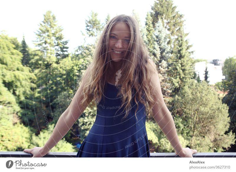 Portrait einer lachenden jungen Frau auf dem Balkon vor Bäumen Blauer Himmel intensiv Mädchen Erwachsene Porträt Tag Haut Sonnenlicht selbstbewußt