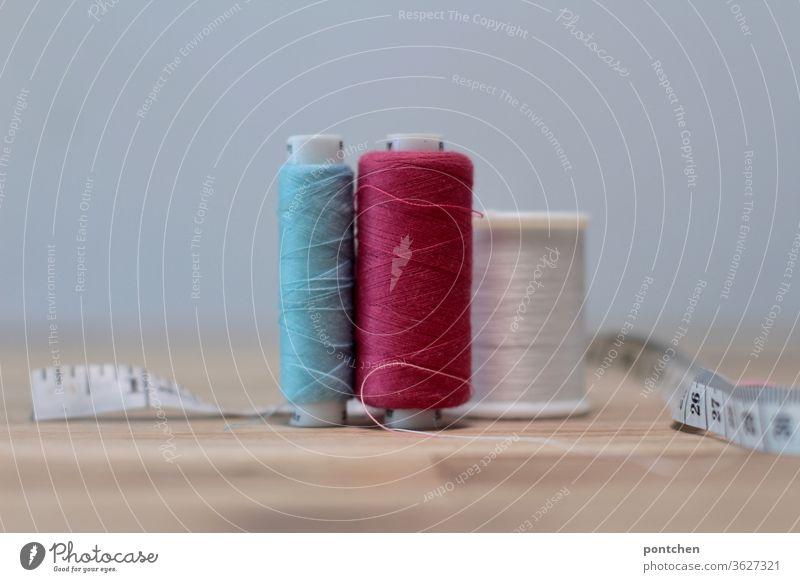 Nähgarne in verschiedenen Farben und ein Maßband auf einem Tisch. Handwerk, Nähen. faden maßband handwerk handarbeiten DIY doityourself farben nähen Handarbeit