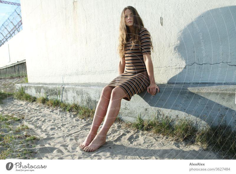 Portrait einer jungen Frau am Strand auf einer Betonmauer intensiv Mädchen Erwachsene Porträt Tag Haut Sonnenlicht selbstbewußt Zentralperspektive Junge Frau