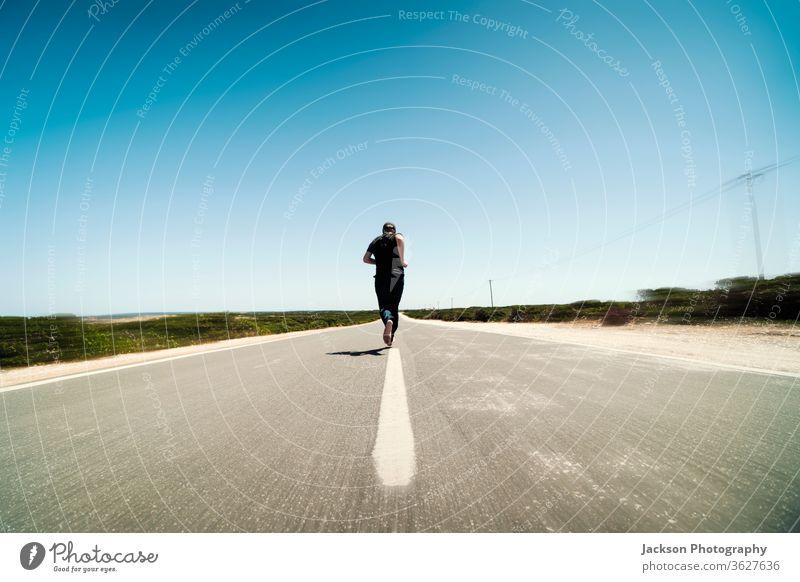 Ein Mann rennt mitten auf der leeren Straße Läufer laufen Textfreiraum Asphalt Konzept Linie Fuß barfüßig unverhüllt Bewegung verschwommen ausgerissen Portugal