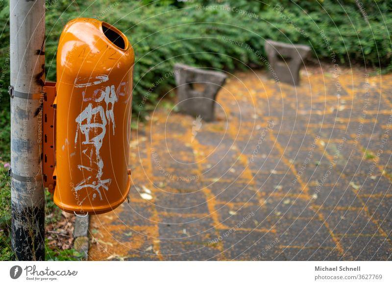 Oranger Mülleimer vor orangenen Blüten auf dem Boden Müllbehälter Umwelt dreckig Müllentsorgung wegwerfen Außenaufnahme