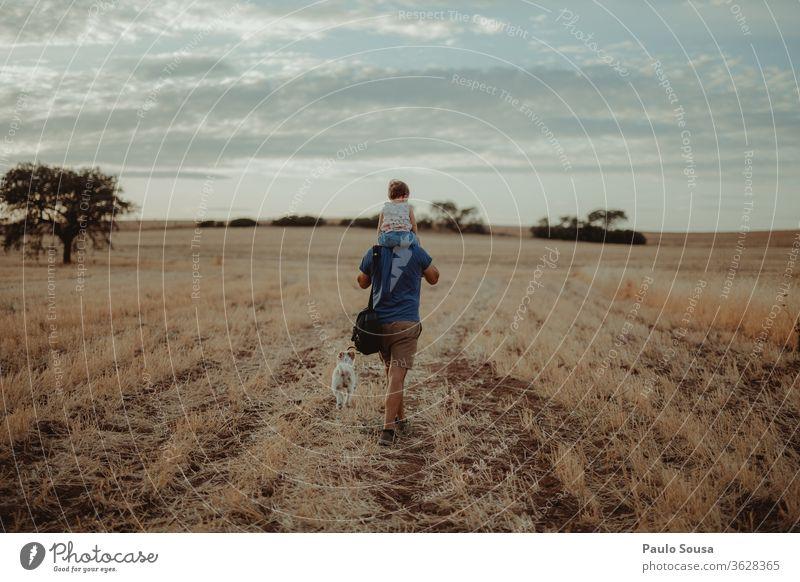 Vater mit Tochter tragen Schulter Schultern laufen Familie & Verwandtschaft Vater mit Kind Feld Sommer Sommerurlaub Reisefotografie reisen Haustier Hund Mann