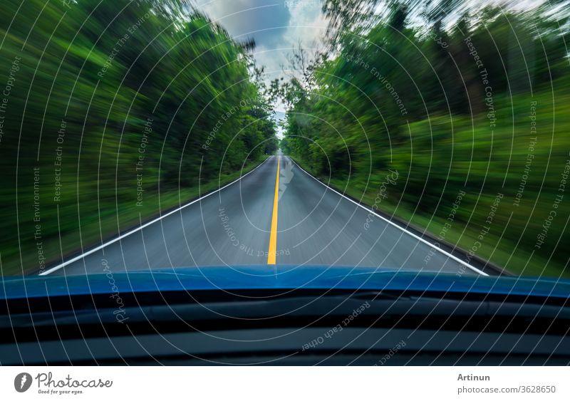 Frontansicht eines blauen Autos, das mit hoher Geschwindigkeit auf der Mitte einer Asphaltstraße mit weißer und gelber Linie des Verkehrssymbols im grünen Wald fährt. Die Bäume neben der Straße sind verschwommen. Auto mit verschwommener Bewegung.