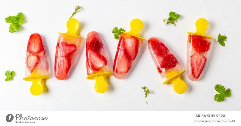 Hausgemachte Erdbeer-Eis am Stiel gefrorener Saft, Eis am Stiel und frische grüne Blätter auf weißem Hintergrund. Leuchtend erfrischender Geschmack des Sommers, Banner