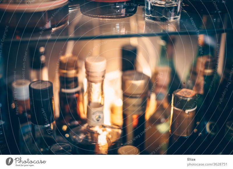 Verschiedene Flaschen mit Schnaps und Likören voller Alkohol in einem Regal in einer Bar. Schnapsflaschen alkoholisch Sammlung Glas Korken beleuchtet Licht