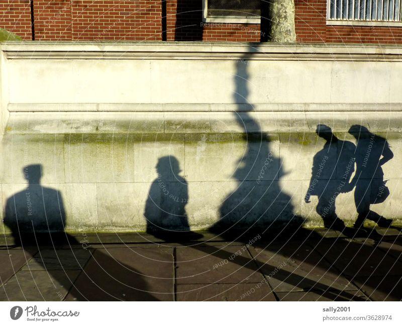 Schattenspiel... Menschen Laternenpfahl Paar Händchenhalten Licht Mann Frau London England Backsteinwand Gehweg Pflasterweg Zusammensein Interaktion