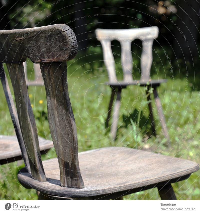Stuhlkreis, Teilansicht Holzstuhl Stuhllehne Stuhlbeine Sitz Sitzgelegenheit alt braun Möbel Gras Wiese grün Menschenleer Einsamkeit