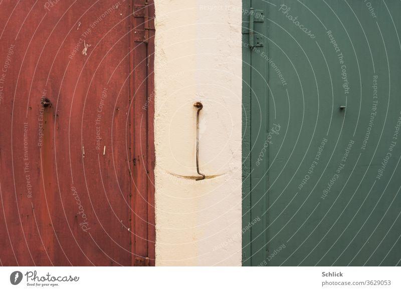 Detail Zwei Eisentüren rot und grün mit Arretierung in der Bildmitte 2 Haken alt Gebrauchsspuren Pendel Ösen Metall Rostschutz Italien Nationalfarben