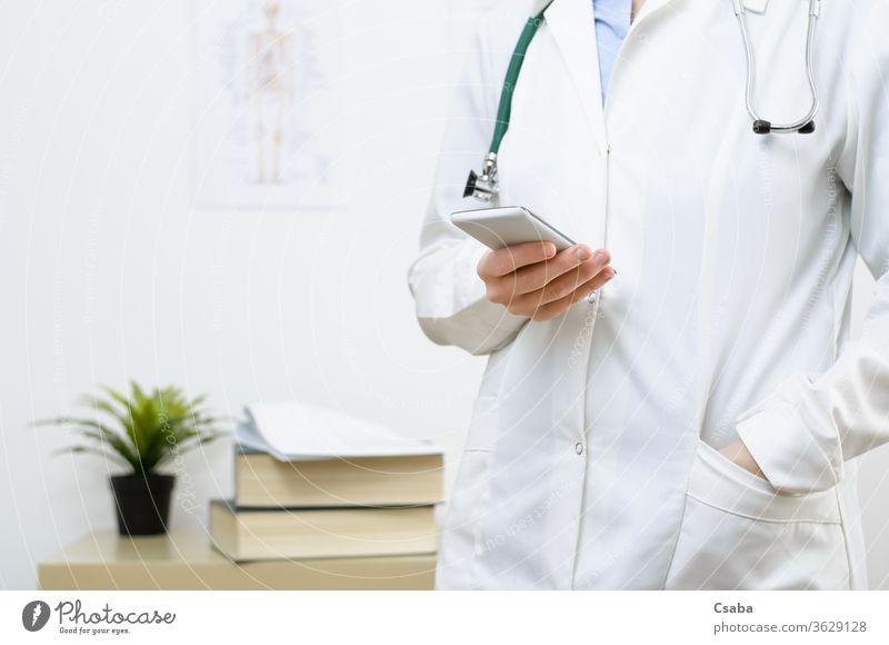 Eine Ärztin schreibt eine SMS auf einem Smartphone Arzt Büro benutzend Technik & Technologie Frau Telefon Hand Funktelefon Texten Tippen Nachricht Beteiligung