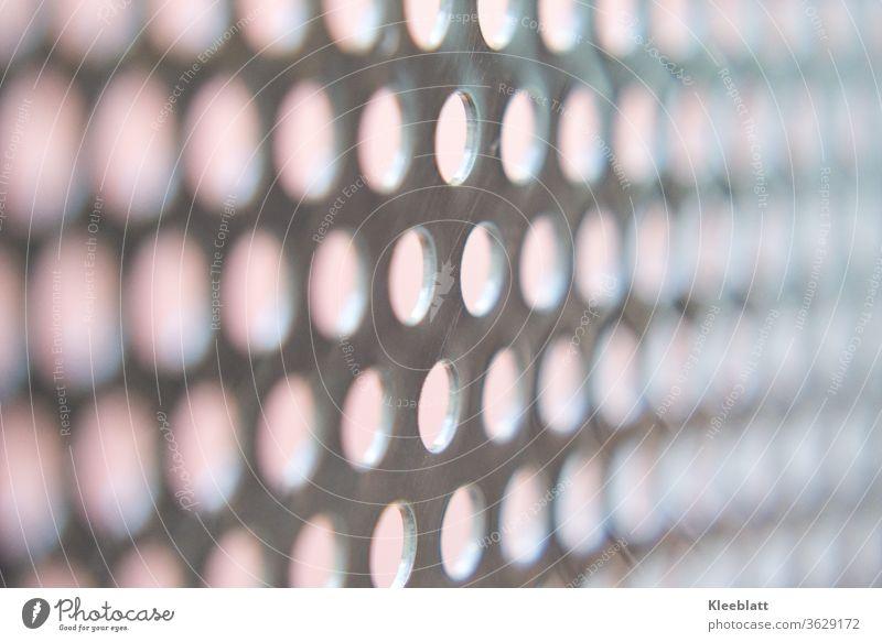 Edelstahllochblech mit hellem Hintergrund, klarer Fokus in der Mitte des Bildes, rechts und links verschommen Lochblech, Metall Muster Detailaufnahme Licht