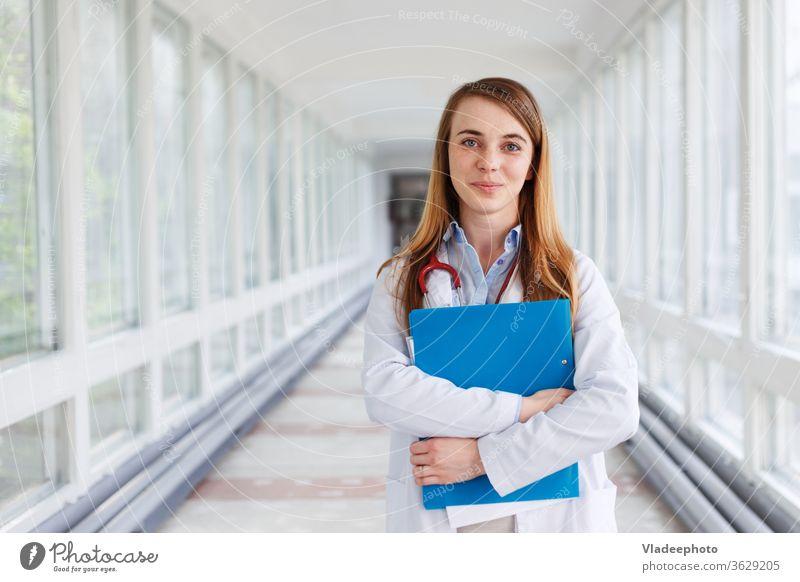 Ärztin über Klinikinterieurs Hintergrund. jung Frau Porträt weiß Lächeln Gesundheit Krankenhaus Praktikant Spezialist Arzt medizinisch Stethoskop Mädchen Job