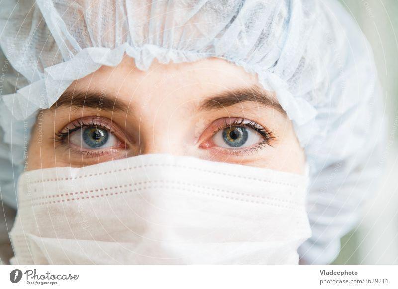 Nahaufnahmeportrait einer jungen Chirurgin oder Assistenzärztin mit Schutzmaske und Hut medizinisch Arzt Chirurgie Frau Mundschutz Porträt Konzept Notfall