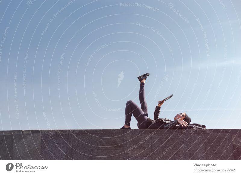Seitenansicht eines Teenagers, der das Tablett an Feiertagen benutzt, im Freien liegend mit klarem Himmel im Hintergrund. Copyspace oben auf dem Rahmen. Straße