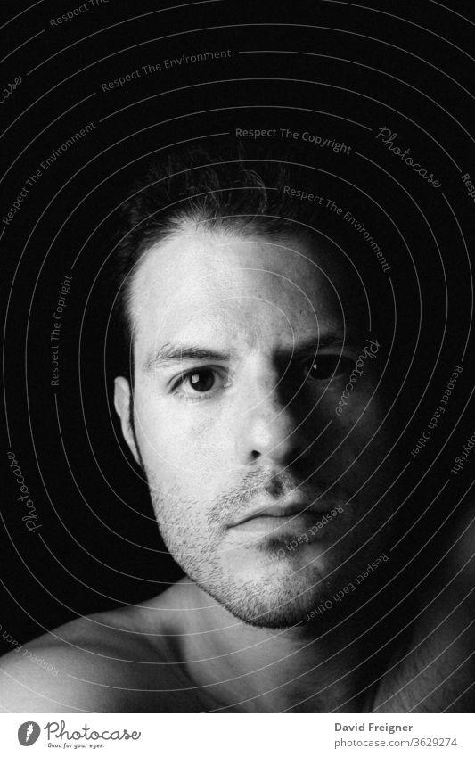Intimes Selbstporträt eines jungen Mannes auf dunklem Hintergrund Menschliches Gesicht dunkel Schatten schwarzer Hintergrund Menschen Nahaufnahme ernst itim