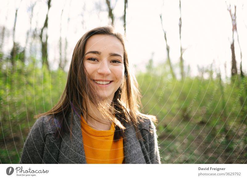 Junge und attraktive Frau, die im Wald steht und lacht. Lifestyle-, Gesundheits- und Umweltschutzkonzept. Vintage-Analogfilm-Look. schön windig Träume Erholung