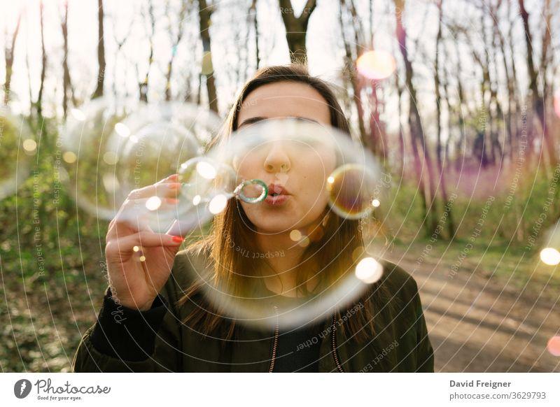 Junge Frau, die im Wald Seifenblasen bläst. verbinden Blasen Vernetzung Schlag Freiheit blasend Tag natürlich hübsch Seifenblasen blasen Porträt farbenfroh