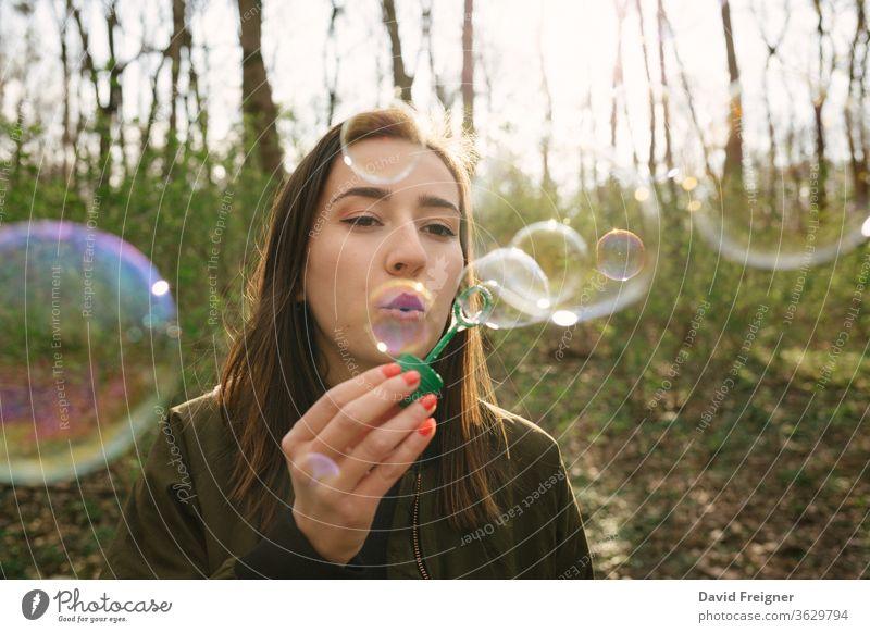 Junge Frau, die im Wald Seifenblasen bläst. Freiheit Blasen blasend Vernetzung Frauen Schlag Menschen Glück nachlässig Spaß Seifenblasen blasen Freizeit