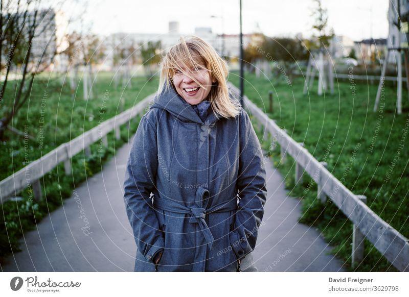 Natürlich blonde glückliche Frau, die in einem herbstlichen Park steht. Herbst-, Outdoor- und Lifestyle-Konzept. Natur Porträt schön Schönheit Kaukasier Glück
