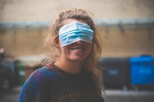 Eine junge Frau trägt die Maske falsch vor den Augen Maskenpflicht Quatsch Mundschutz Weigerung albern blind verdeckt bedeckt Corona genervt lächeln